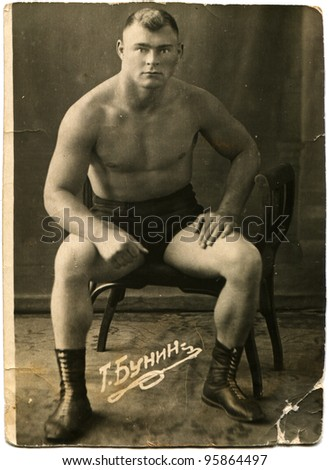 USSR - CIRCA 1930s: Studio portrait of a fighter, sitting on a chair, circa 1930s, Russian text - T Bunin - stock photo