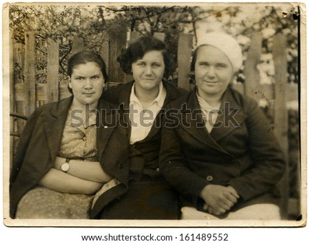 USSR - CIRCA 1939: three women sitting near the fence, behind which blooms garden, Mineralnye Vody, the Caucasus, USSR, May 1, 1939 - stock photo
