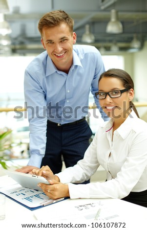 Usual working day at business agency, boss checking the work of his lovely subordinate - stock photo