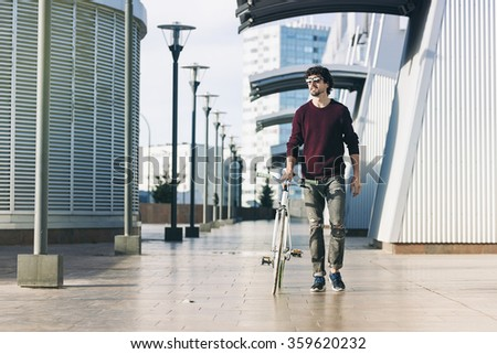 utdoor portrait of handsome young man with fixed gear bicycle in the street. - stock photo