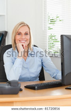 ute blonde woman with chin on hand behind a desk looking at screen in an office - stock photo