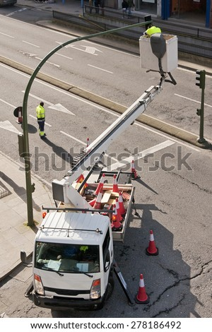 utility service company electrician worker repairs traffic lights from elevator bucket truck in the city - stock photo