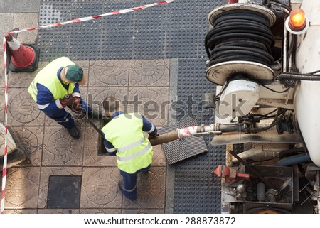 utility service company worker cleaning the city street  with water pressure  - stock photo