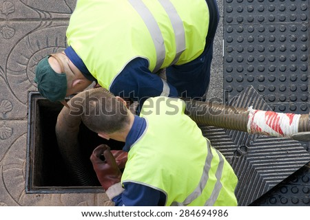 utility service company workers moves the manhole cover to cleaning the sewer line for clogs aerial view  - stock photo