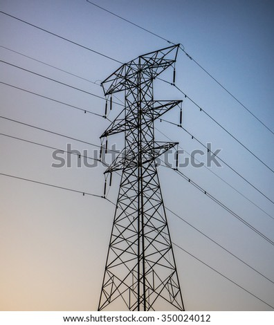 Utility tower silhouetted against blue sky at sunset