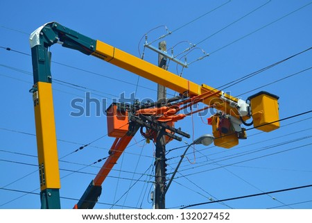 Utility workers repairing some power lines in the city of Hamilton Ontario, Canada, under blue sky. - stock photo