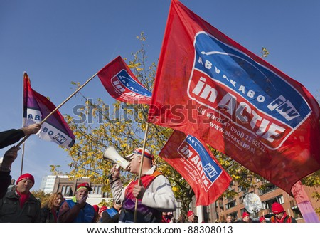 UTRECHT, THE NETHERLANDS  - NOVEMBER 1: Unidentified member of the Dutch civil servants trade union (AbvaKabo) waves a flag during a protest on November 1, 2011 in Utrecht, The Netherlands. - stock photo