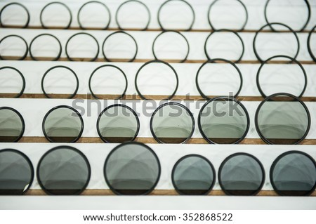 UV filter, Photographic camera equipment filter to protect lens that arrange several size and several shade with shadow in line for show.in all background - stock photo