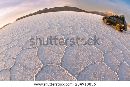 UYUNI - NOVEMBER  12:Tourists move on salt   desert Uyuni on off-road car  on November  12, 2014 in Uyuni, Bolivia. Desert Uyuni is one of the greatest salt deserts in the world - stock photo