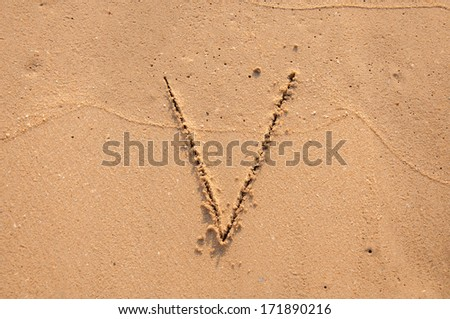 V text written in the sandy on the beach - stock photo