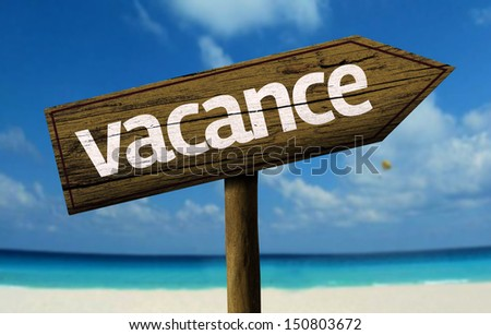 Vacance - Vacation in French - wooden sign with a beach on background  - stock photo
