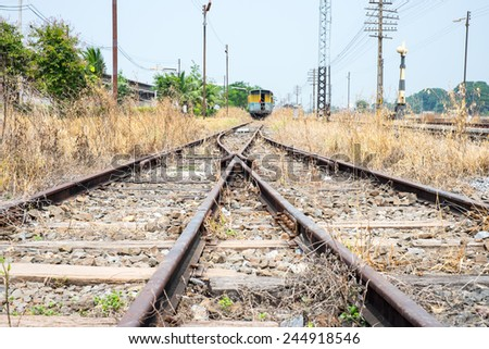 Vacant Rail way switch track with yellow die grass - stock photo