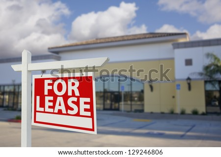 Vacant Retail Building with For Lease Real Estate Sign in Front. - stock photo