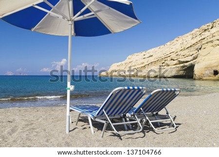 Vacation and Tourism concept. Two blue striped deck chairs and a parasol on a sandy beach - stock photo