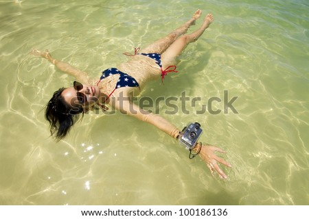 vacation, Asian woman floating in the ocean wear sunglasses and bikini - stock photo