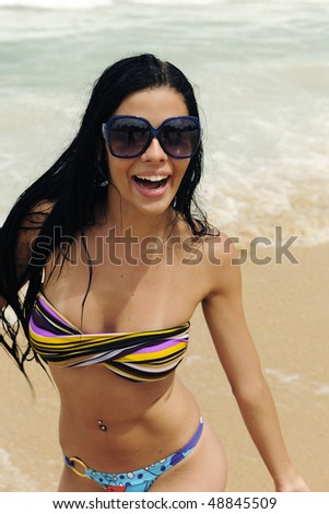 vacation: attractive girl with sunglasses on the beach - stock photo
