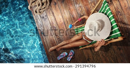 Vacation. Beautiful young woman relaxing on beach chair with cocktail. Top view - stock photo