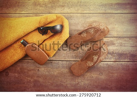 Vacation Concept. Orange towel and beach items on wood background - stock photo