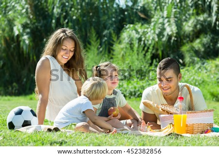 Vacation day of happy young family with picnic at countryside in summer day
