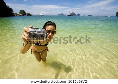 vacation girl, live Asian girl hold camera on the bikini beach - stock photo