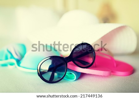 vacation, holiday and travel concept - close-up of bikini top, straw hat, flip-flop and sunglasses on hotel bed - stock photo