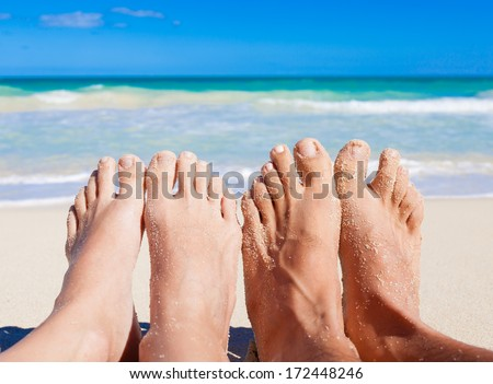 Vacation holiday. Close up of young couple feet relaxing on beach. - stock photo