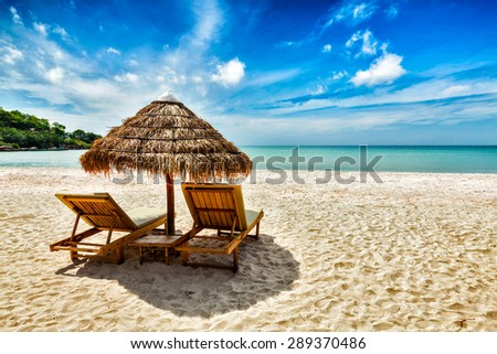 Vacation holidays background wallpaper - two beach lounge chairs under tent on beach. Sihanoukville, Cambodia - stock photo