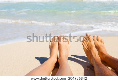 Vacation holidays. Close up of girl's and boy's feet on the beach. - stock photo