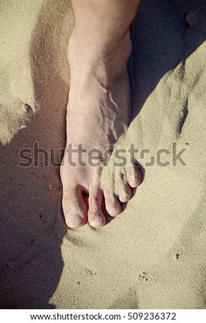 Vacation holidays. Feet closeup on beach on sunbed enjoying sun on sunny summer day.