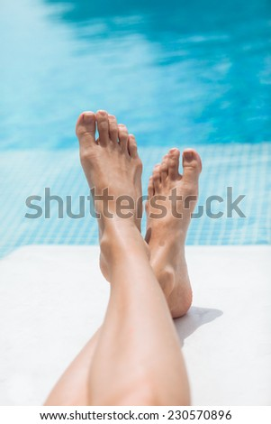 Vacation holidays. Feet relaxing by the pool - stock photo