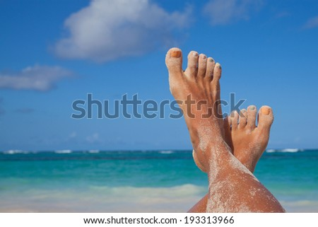 Vacation holidays. Woman feet closeup of girl relaxing on exotic beach, enjoying sun on sunny summer day.