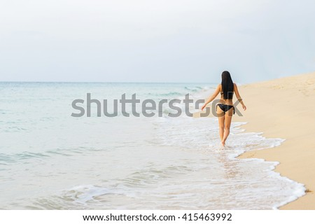 Vacation on the sea. Young sexy caucasian woman walk on ocean beach. Back  view. - stock photo