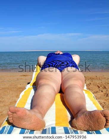 vacation - overweight woman lying on beach - stock photo