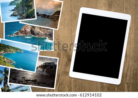 Vacation pictures on a wooden table and blank screen tablet. View from above.