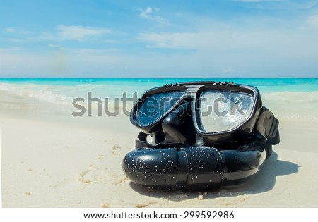 Vacation Start Here Concept, Scuba Diving Equipment On The White Sea Sand Beach with Crystal Clear Sea and Sky in Background used as Template - stock photo