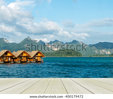 Vacation Start Here Concept, Wooden Perspective Floor with Beautiful Wooden Floating House in Peaceful View of Ratchaprapa dam , Khao sok national park,Thailand use to Mock up or Display Product