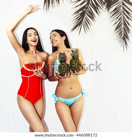 Vacation. Summer travel. Two beautiful sexy brunette girls outdoor with watermelon and pineapples in bikini on white wall background with palm tree shadow having fun laugh smile at the beach - stock photo