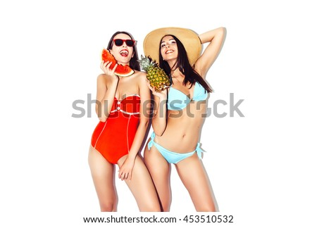 Vacation. Summer travel. Two beautiful sexy brunette girls outdoor with watermelon and pineapples in bikini on white background having fun laugh smile at the beach. Isolated white background - stock photo