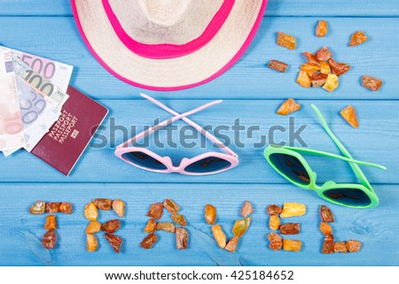 Vacation time. Inscription travel and shape of sun made of amber stones, sunglasses and straw hat, passport with currencies euro