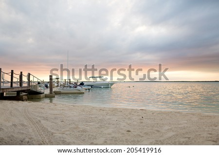 vacation, travel and sea concept - boats moored to pier at sundown - stock photo