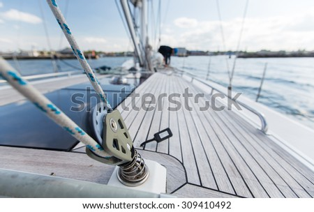 vacation, travel, cruise and leisure concept - close up of sailboat winch or yacht deck sailing on sea - stock photo