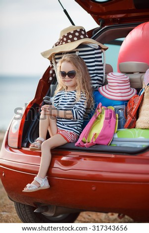 Vacation, Travel - family ready for the travel for summer vacation. suitcases and car with sea on background. girl with map in hands planning road trip. travel concept. traveler. - stock photo