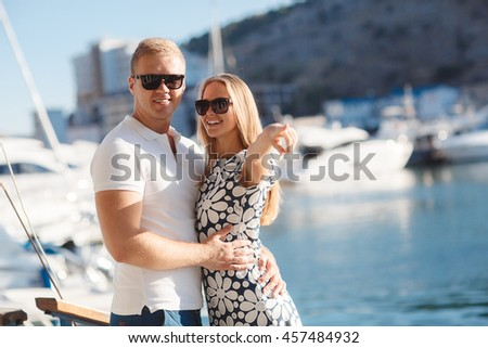 vacation, travel, sea, friendship and people concept - smiling couple by sea yachts. love, travel, tourism and people concept - smiling couple wearing sunglasses walking at harbor. rich and attractive - stock photo