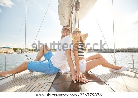vacation, travel, sea, friendship and people concept - smiling couple sitting and talking on yacht deck - stock photo