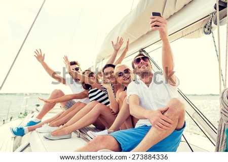 vacation, travel, sea, friendship and people concept - smiling friends sitting on yacht deck and making selfie - stock photo