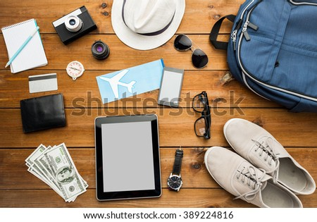 vacation, travel, tourism, technology and objects concept - close up of gadgets and traveler personal stuff - stock photo