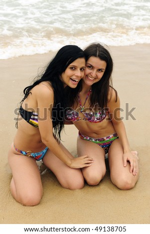 vacation: two beautiful young women on the beach - stock photo
