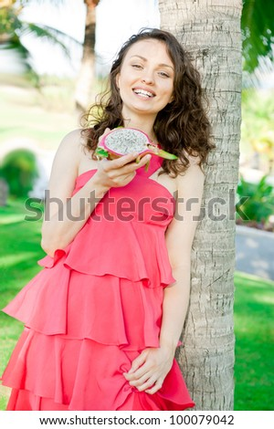 Vacation woman enjoying exotic fruit in tropical resort. Gorgeous Caucasian young woman in elegant pink dress during summer holidays.