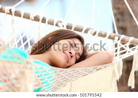 Vacation woman lying in hammock relaxing and sleeping smiling happy during summer holidays in tropical resort. Mixed race Asian / Caucasian girl in bikini. - stock photo