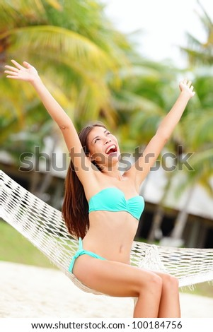 Vacation woman on beach happy and joyful with arms raised sitting in hammock. Beautiful young bikini model in summer holidays resort. Mixed race Caucasian / Chinese Asian woman. - stock photo